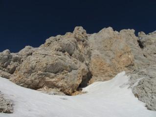 Vhod v Ivačičevo jamo je nad strmim snežiščem pod Kredarico